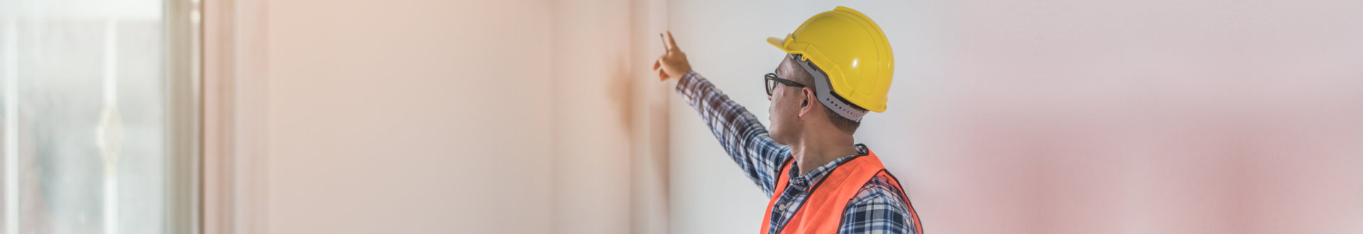 construction worker pointing to the wall